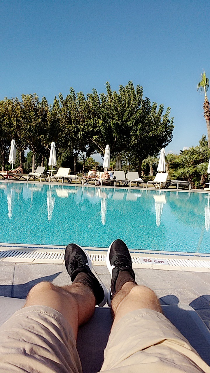 A photo showing me chilling at the pool but wearing shoes