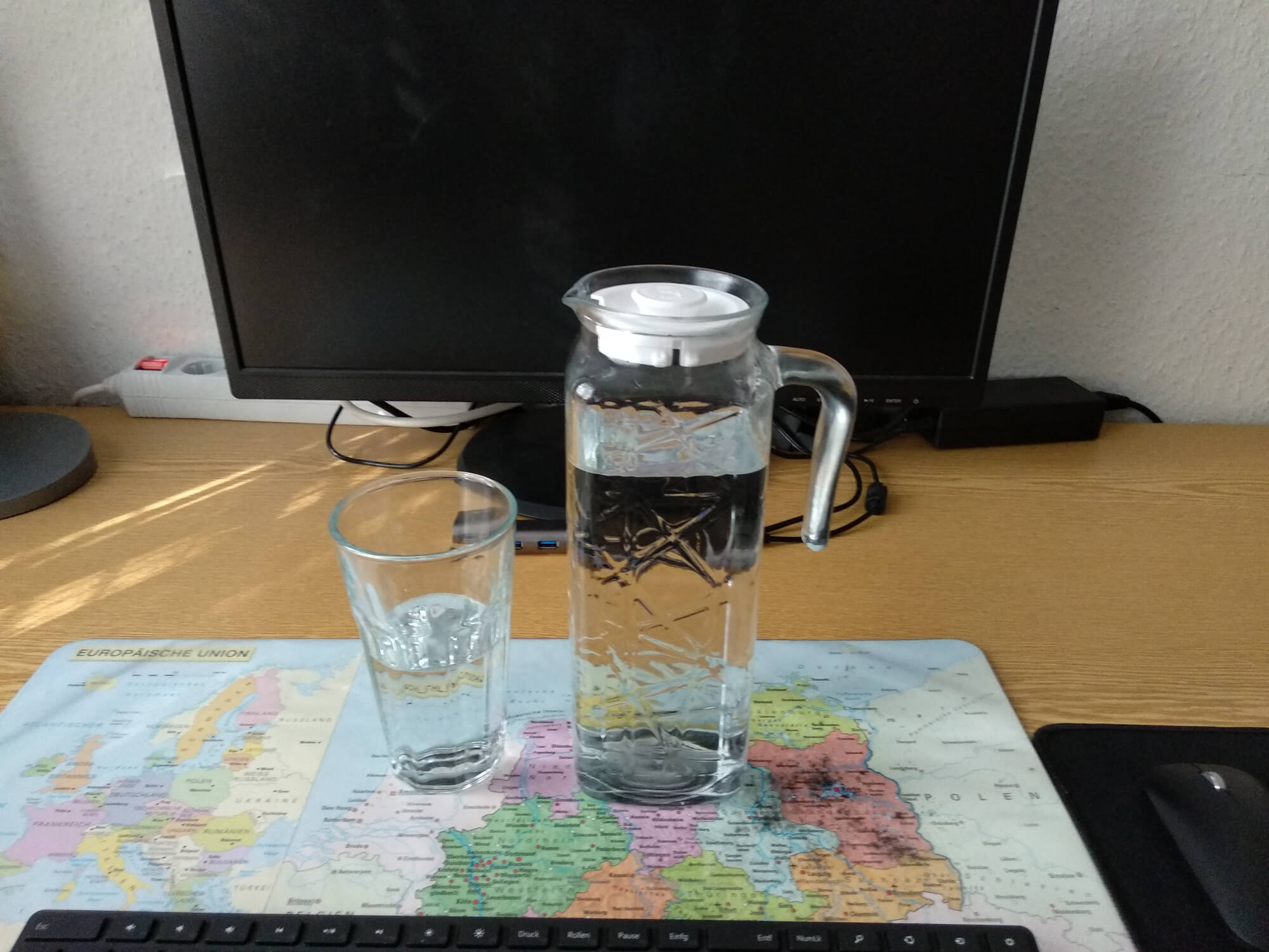 A glass jug with water and a glass with water on my desk
